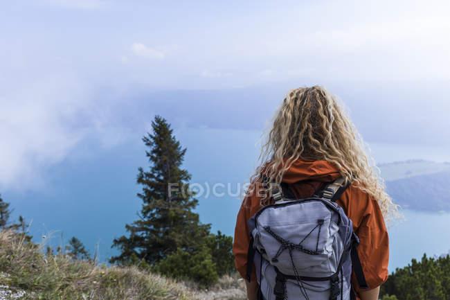 Mujer joven senderismo en las montañas de Baviera, mirando el lago Walchensee - foto de stock