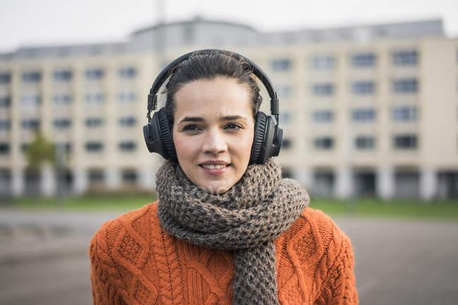 Портрет улыбающейся женщины, носящей шарф и апельсиновый вязаный пуловер, слушающей музыку в наушниках — стоковое фото