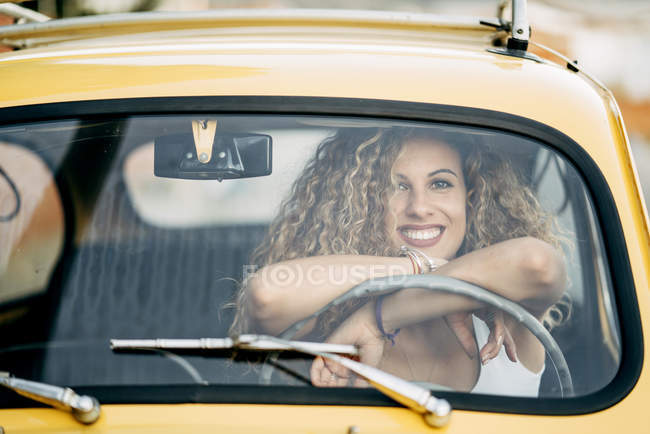 Portrait of happy blond woman in a classic car — Stock Photo