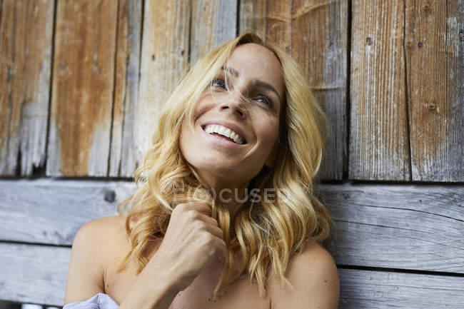 Портрет счастливой блондинки перед деревянной стеной — стоковое фото