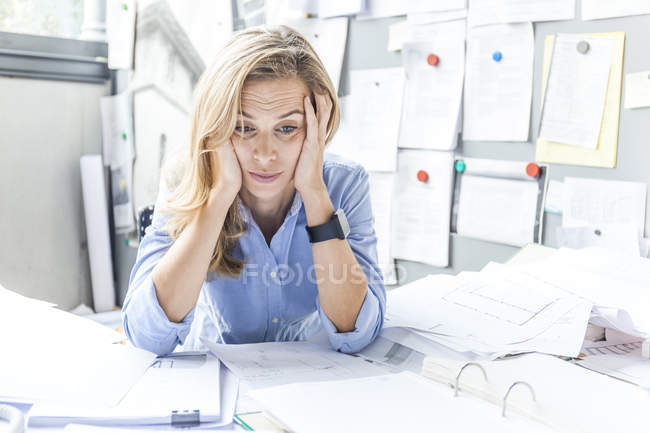 Stressed woman sitting at desk in office surrounded by paperwork — Stock Photo
