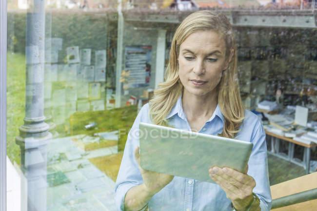 Жінка, використовуючи планшет в офісі за Шибка — стокове фото