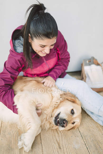 Happy young woman stroking and playing with her golden retriever dog — Stock Photo