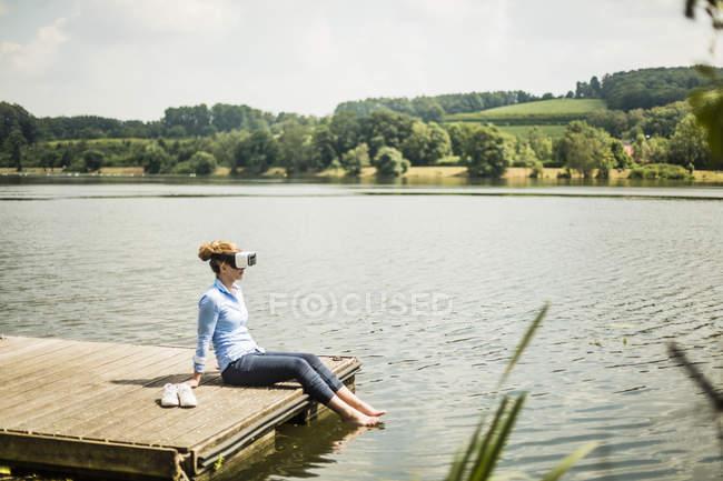 Frau mit Vr-Brille sitzt auf Steg an einem See mit Füßen im Wasser — Stockfoto