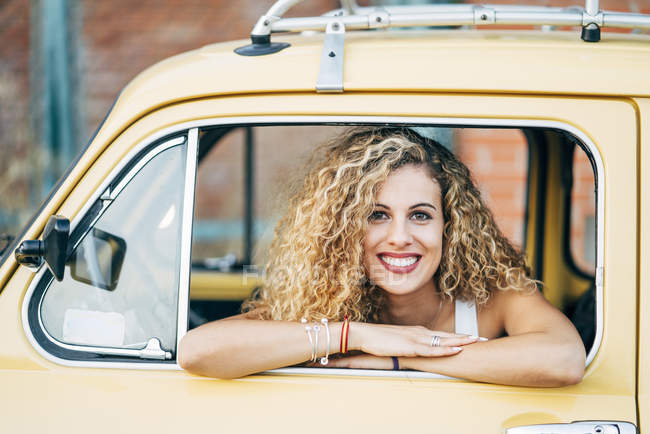 Portrait of happy blond woman looking out of window of classic car — Stock Photo