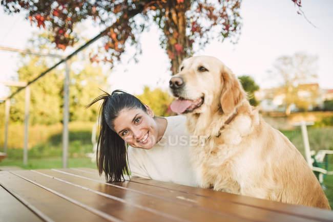 Ritratto di giovane donna felice con il suo cane Golden retriever che riposa in un parco — Foto stock