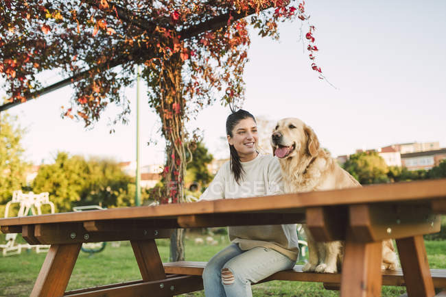 Smiling young woman with her Golden retriever dog resting in a park — Stock Photo