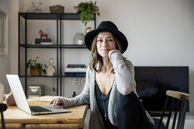 Mature woman with hat, sitting at home, using laptop — Stock Photo