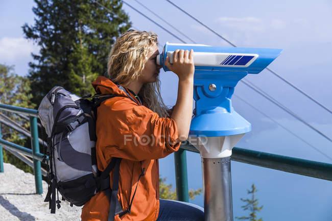 Jovem mulher olhando para as montanhas, usando o telescópio operado por moedas — Fotografia de Stock