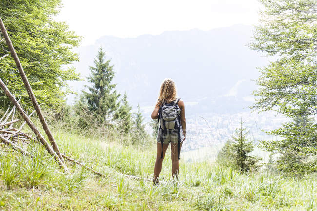 Germany, Bavaria, Oberammergau, young woman standing on mountain meadow — Stock Photo