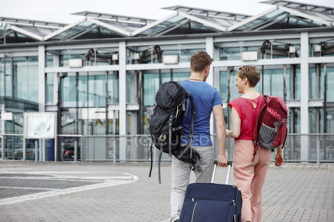 Vue arrière du couple marchant à l'extérieur de l'aéroport — Photo de stock