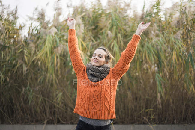 Portrait of smiling woman wearing orange knit pullover and scarf in autumn — Stock Photo