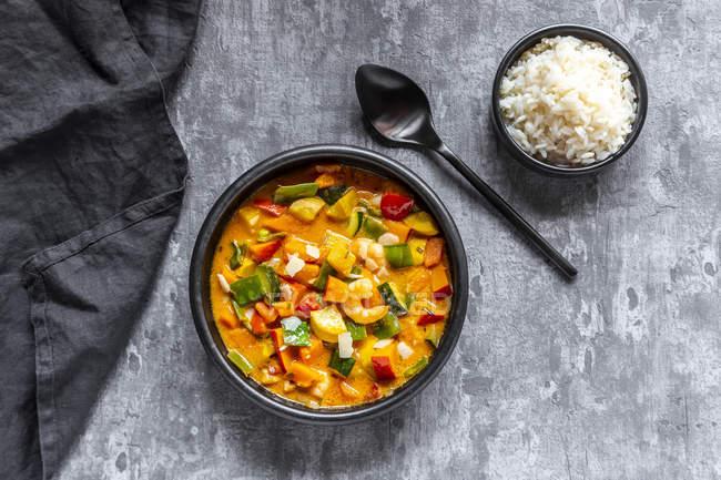 Plato de curry, curry de batata, guisante de azúcar, pimentón, calabacín, leche de coco, camarones y arroz - foto de stock