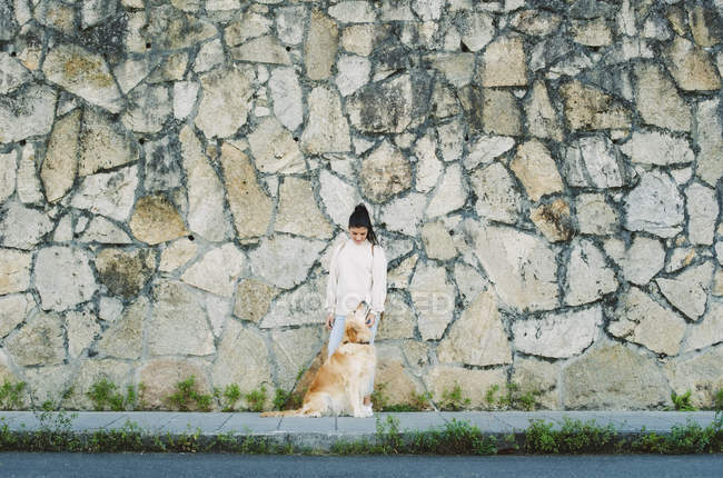 Young woman with her Golden retriever dog at a stone wall — Stock Photo