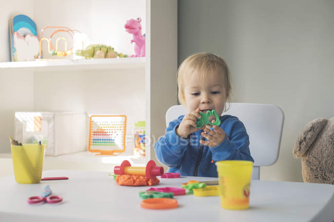 Portrait of baby girl playing with cutter and modeling clay — Stock Photo