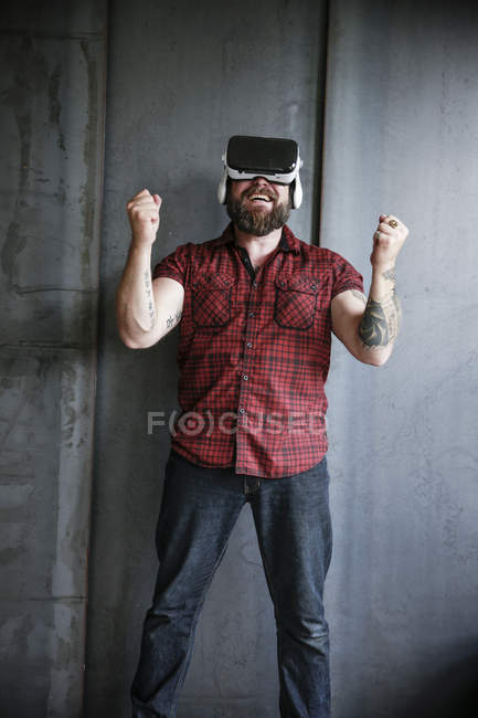 Happy, winner Bearded man wearing VR glasses at grey wall — Stock Photo