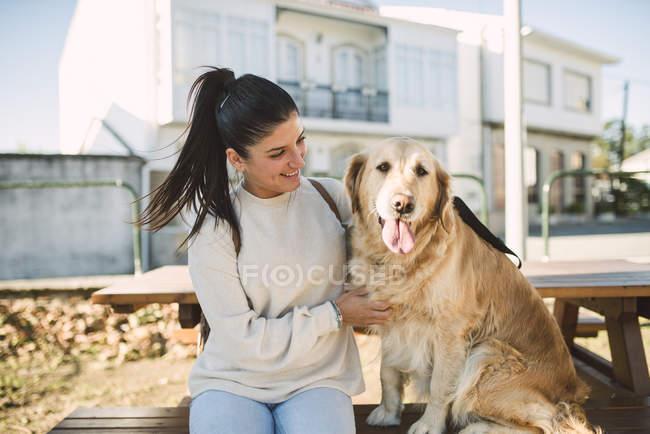 Улыбающаяся молодая женщина со своей золотистой собакой-ретривером отдыхает на улице — стоковое фото