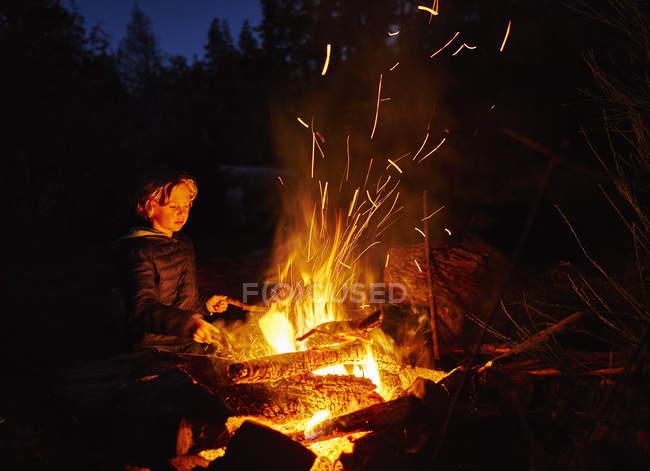 Argentina, Patagonia, Lago Futalaufquen, boy at camp fire at night — Stock Photo
