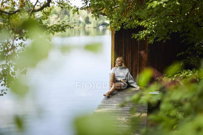 Расслабленная женщина, сидящая на деревянной пристани на удаленном озере — стоковое фото