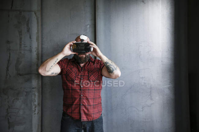 Bearded man wearing and adjusting VR glasses at grey wall — Stock Photo