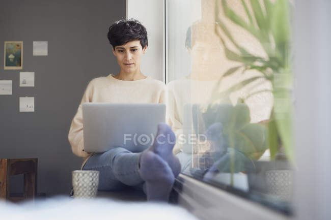 Woman at home sitting at the window and using laptop — Stock Photo