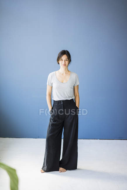 Womans standing barefoot with hands in pocket in front of blue background — Stock Photo
