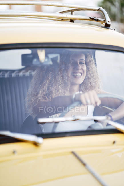 Portrait of laughing blond woman driving classic car — Stock Photo