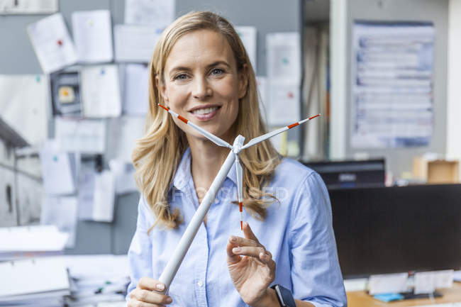 Portrait of smiling woman in office holding wind turbine model — Stock Photo