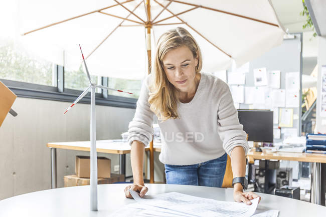 Woman in office working on plan with wind turbine model on table — Stock Photo