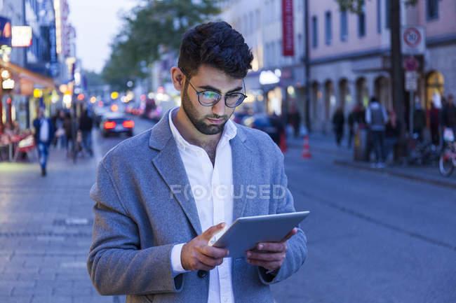 Alemania, Múnich, joven empresario usando tableta digital en la ciudad al atardecer - foto de stock