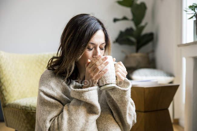 Mujer sentada en su cómoda casa, bebiendo té - foto de stock