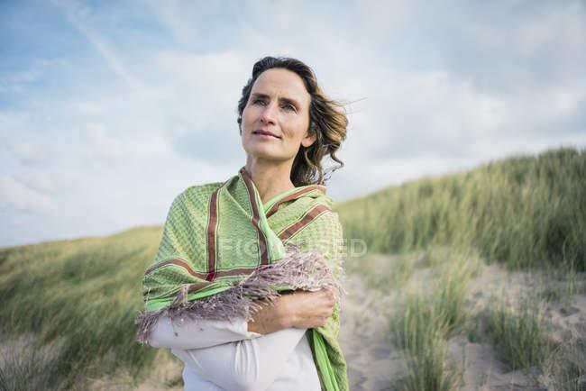Reife Frau steht in den Dünen, Blick auf die Entfernung — Stockfoto