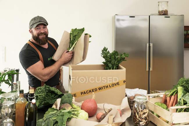 Hombre maduro con servicio de entrega de verduras orgánicas en cartón - foto de stock
