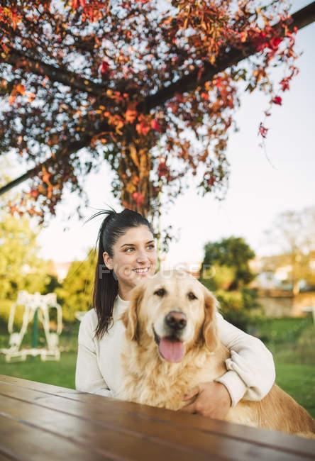 Sorridente giovane donna con il suo cane Golden retriever che riposa in un parco — Foto stock