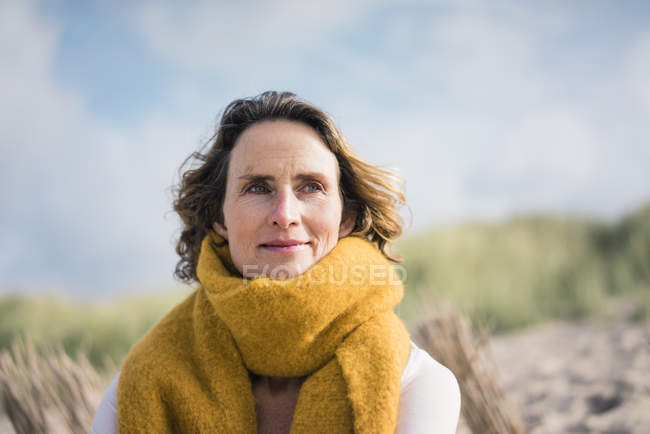 Donna matura rilassante tra le dune, godendo del vento — Foto stock