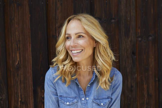 Glückliche blonde Frau vor hölzerner Wand — Stockfoto