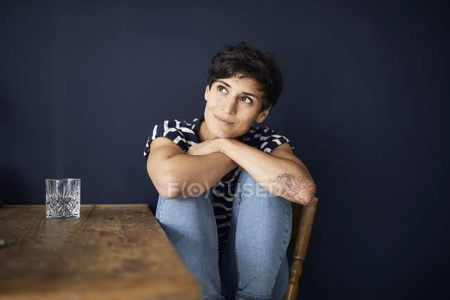 Портрет женщины дома, сидящей за деревянным столом — стоковое фото