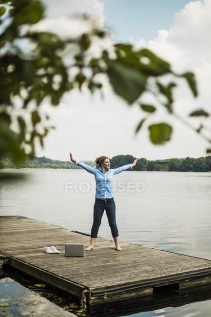 Frau streckt sich auf Steg an einem See neben Laptop — Stockfoto