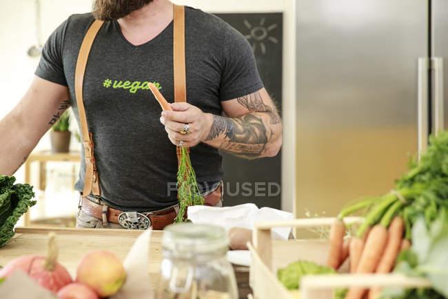 Cenoura da terra arrendada do homem do vegan em sua cozinha, imagem cortada — Fotografia de Stock