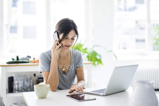Happy woman sitting at desk, working from home, using laptop — Foto stock