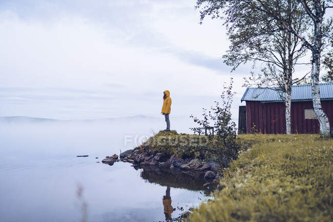 Sweden, Lapland, man wearing  windbreaker standing at water edge looking at distance — Stock Photo