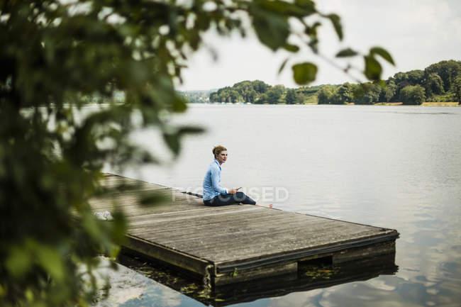 Frau sitzt auf Steg an einem See und entspannt — Stockfoto
