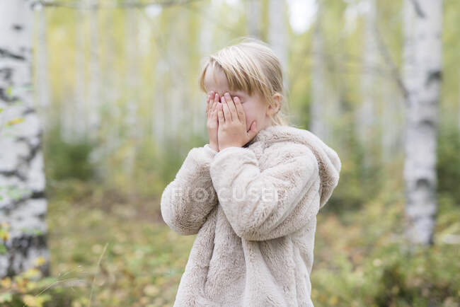 Menina loira jogar Esconder e procurar em uma floresta — Fotografia de Stock