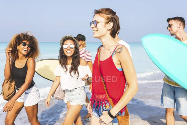Grupo de amigos caminando por la playa, llevando tablas de surf - foto de stock