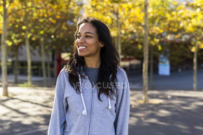 Retrato de uma mulher sorridente, de pé em um parque — Fotografia de Stock