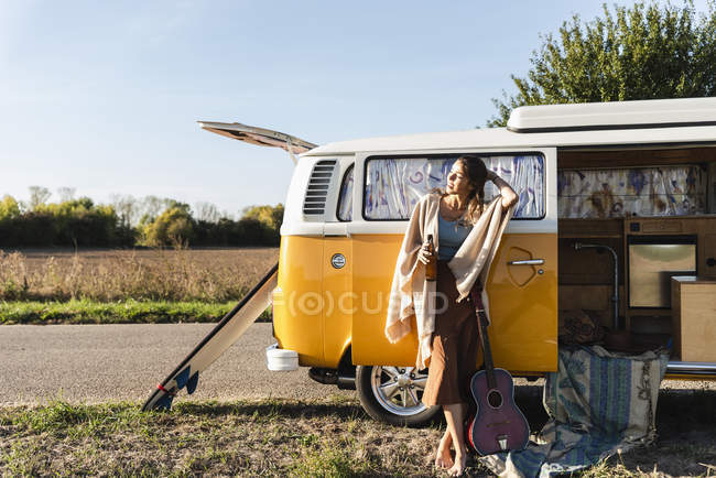 Pretty woman on a road trip with her camper, drinking beer, holding guitar — Stock Photo