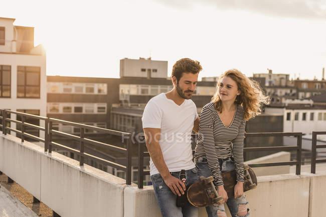 Giovane coppia rilassante sulla terrazza sul tetto al tramonto — Foto stock