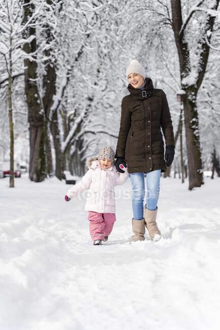 Щаслива мати ходить з дочкою в зимовий краєвид. — стокове фото