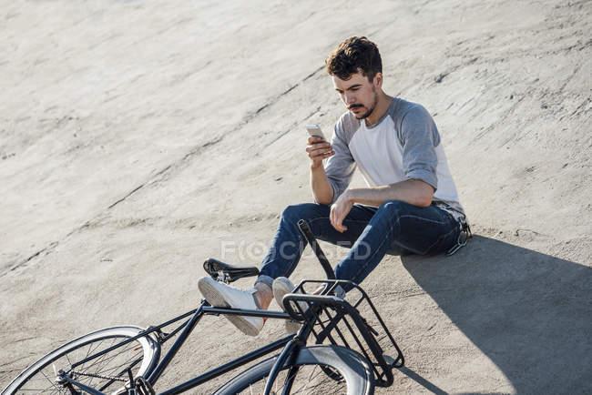 Jovem com pendulares fixie bike sentado na parede de concreto e usando telefone celular — Fotografia de Stock