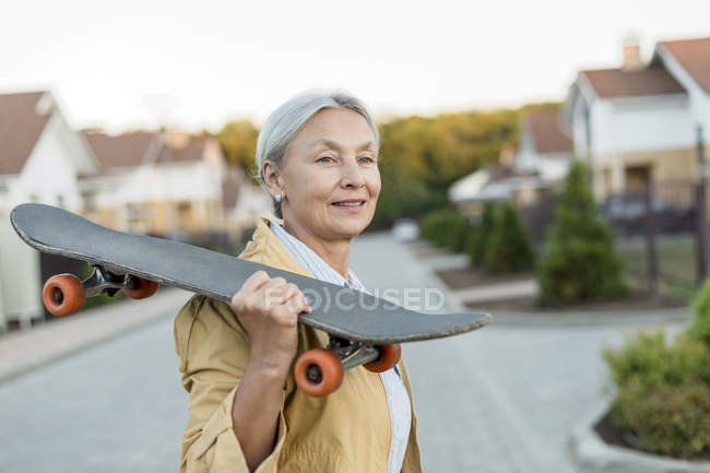 Portrait of smiling senior woman with skateboard on her shoulder — Stock Photo